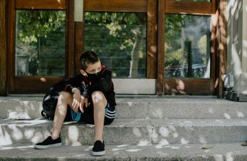Child sits on steps with backpack, wearing a non-medical mask